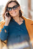 Happy pretty woman in sunglasses talking on mobile phone stock image