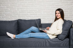 Happy pretty woman using laptop sitting on cosy sofa at home Royalty Free Stock Photos