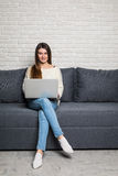 Happy pretty woman using laptop sitting on cosy sofa at home Stock Photography