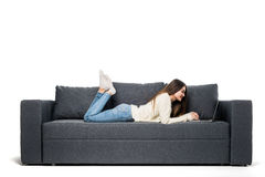 Happy pretty woman using laptop sitting on sofa Stock Image