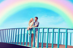 Happy pretty young couple in love on the bridge over blue sky and colorful rainbow. Valentine`s day and relationships stock photography