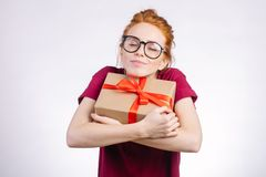 Happy redhead woman in glasses holding gift box on white background royalty free stock photo