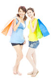 Happy pretty young sisters holding shopping bags. Isolated on white Stock Photography