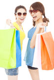 Happy pretty young sisters holding shopping bags. In studio Royalty Free Stock Photo