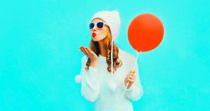 Happy pretty young woman blowing red lips sends air kiss holding stock image