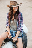 Happy pretty young woman cowgirl riding a horse outdoors. Portrait of happy pretty young woman cowgirl riding a horse outdoors Royalty Free Stock Images