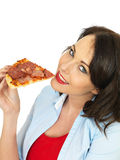 Happy Pretty Young Woman Eating a Slice of Baked Pepperoni and Ham Pizza Stock Images