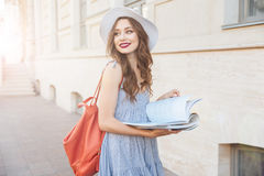 Happy pretty young woman reading a book on the street. Happy pretty young women in hat with backpack standing and reading a book on the street Stock Photography