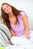 Happy pretty young woman sitting on couch at home Stock Image