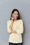 Happy pretty young woman standing and talking on mobile phone Royalty Free Stock Photos