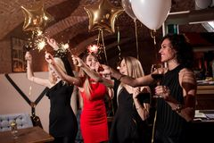Happy pretty young women holding firework sparklers, balloons, glasses of wine celebrating a holiday in restaurant with stock images
