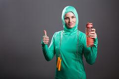 Happy pride athlete muslim woman in green hijab or islamic sport. Swear standing, holding water bottle or shaker, looking at camera with thumbs up. indoor studio royalty free stock photo