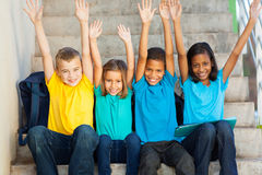 Happy primary students. Group of happy primary students with hands raised sitting outdoors royalty free stock photos