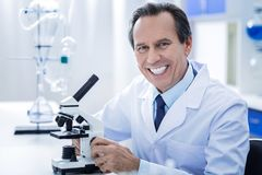 Happy professional biologist working in the lab. Microbiological studies. Happy smart professional biologist smiling and looking at you while working in the lab stock image