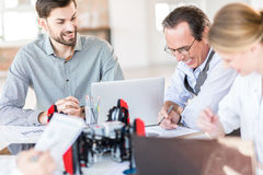 Happy professional team is sitting at table and laughing. Feel positively. Cheerful group of engineers are working in office with smile while creating robots Stock Photography