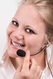 Happy, smiling professional woman with headset. Happy professional woman with headset, in front of white background wearing a white shirt Royalty Free Stock Photography