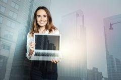 Happy professional woman holding a laptop. Electronic device. Happy professional delighted woman holding a laptop and smiling while looking at you stock image