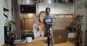 Happy professional young blonde female travel blogger using camera to film new vlog video at home slow motion. Cheerful vlogger woman making a new tutorial stock video