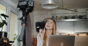 Happy professional young caucasian fashion blogger filming new vlog video with camera at home kitchen slow motion. Blogging and freelance work, popular stock video footage