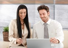 Happy professionals using laptop Stock Photography
