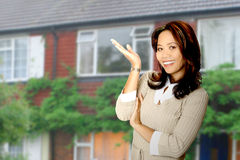 Happy property agent. Attractive and friendly housing agent presenting a beautiful property in her background Royalty Free Stock Photography
