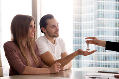 Happy property owners just bought flat, getting house keys indoo. A hand of female real estate agent giving keys to own first apartment to couple, finishing real Royalty Free Stock Photography