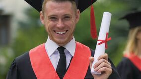 Happy and proud graduating student holding higher education certificate in hand. Stock footage stock video footage