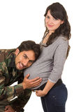 Happy proud military soldier hugging pregnant wife. Listening to belly isolated on white stock photo