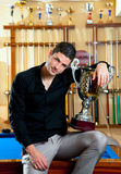 Happy proud winner man with big trophy silver cup. In billiard club royalty free stock image