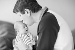 Happy proud young father having fun with newborn baby daughter, family portrait togehter. Dad with baby girl, love. New. Born child looking on dad. Bonding royalty free stock photos