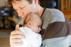 Happy proud young father having fun with newborn baby daughter, family portrait togehter. Dad with baby girl, love. New Stock Image