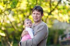 Happy proud young father having fun with newborn baby daughter, family portrait togehter. Dad with baby girl outdoors Royalty Free Stock Image