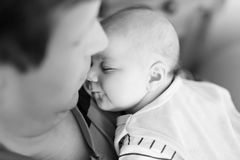 Happy proud young father holding little sleeping baby daughter, family portrait together. Royalty Free Stock Images