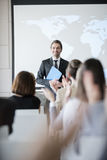 Happy public speaker looking at audience applauding during seminar Royalty Free Stock Photo