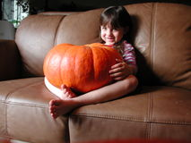 Happy Pumpkin Girl. Little girl smiles and holds a big orange pumpkin on her lap Stock Image