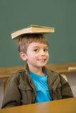Happy pupil balancing book on his head at desk Royalty Free Stock Photo