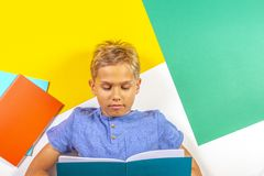 Happy pupil boy reading book notebook. Top view, colorful background Royalty Free Stock Photo