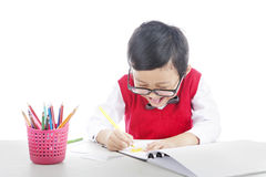 Happy pupil drawing with crayons Stock Photo