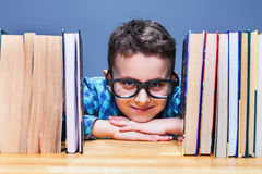 Happy pupil in glasses against books Stock Photo