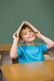 Happy pupil holding book on his head at desk Royalty Free Stock Image