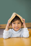 Happy pupil holding book on his head at desk Royalty Free Stock Photography
