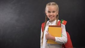 Happy pupil holding books with Portugal flag, ready to learn foreign language. Stock footage stock video footage