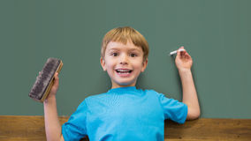 Happy pupil holding chalk and duster in classroom Royalty Free Stock Images