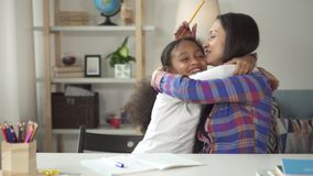 Happy pupil hugs her teacher after success in writing and learning. Playful education for adolescence student is the best way of education. Joy, happyness and stock video footage