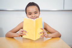 Happy pupil reading from a book Stock Images
