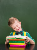 Happy pupil reading a book near empty green chalkboard.  Royalty Free Stock Images