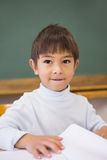 Happy pupil sitting at desk in classroom Royalty Free Stock Photography