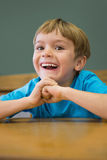 Happy pupil sitting at desk in classroom Royalty Free Stock Images