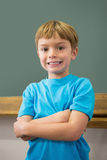 Happy pupil smiling at camera in classroom Stock Photo