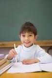 Happy pupil smiling at camera at desk Stock Photos